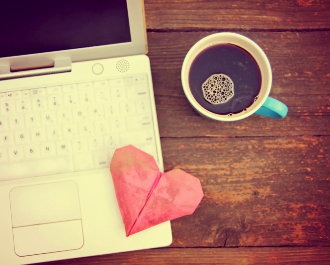 Laptop or notebook with cup of coffee and origami heart on old wooden table toned with a retro vint